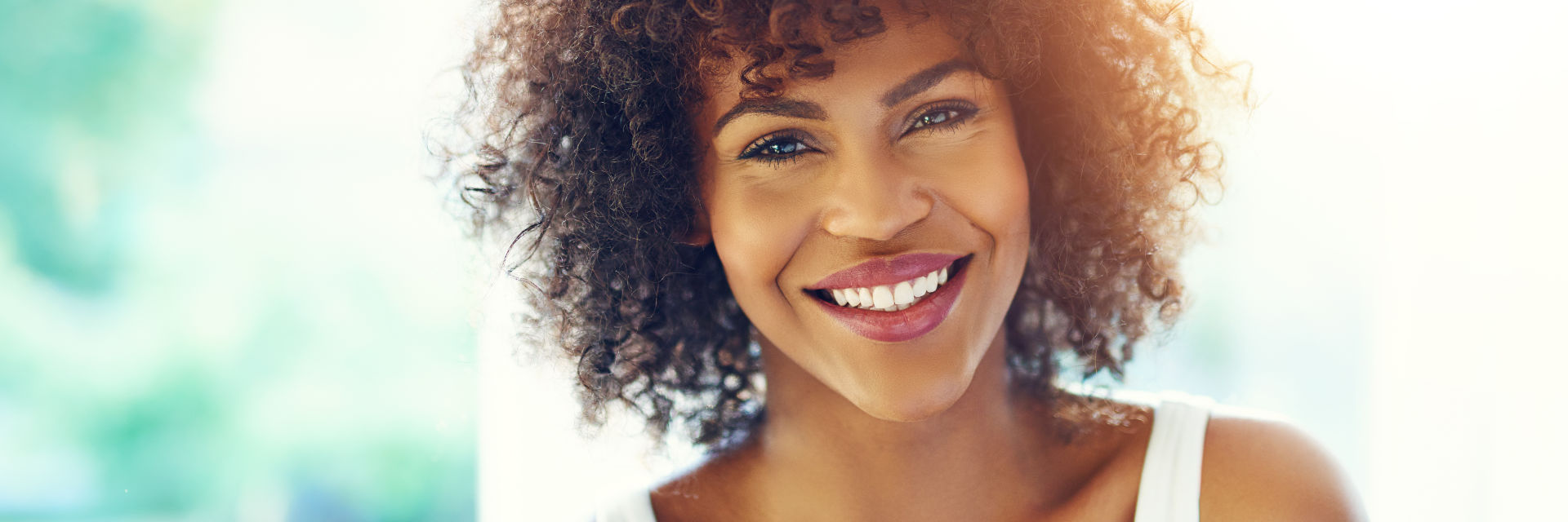 A beautiful middle-aged Afro-American woman showing her perfect teeth in her smile.