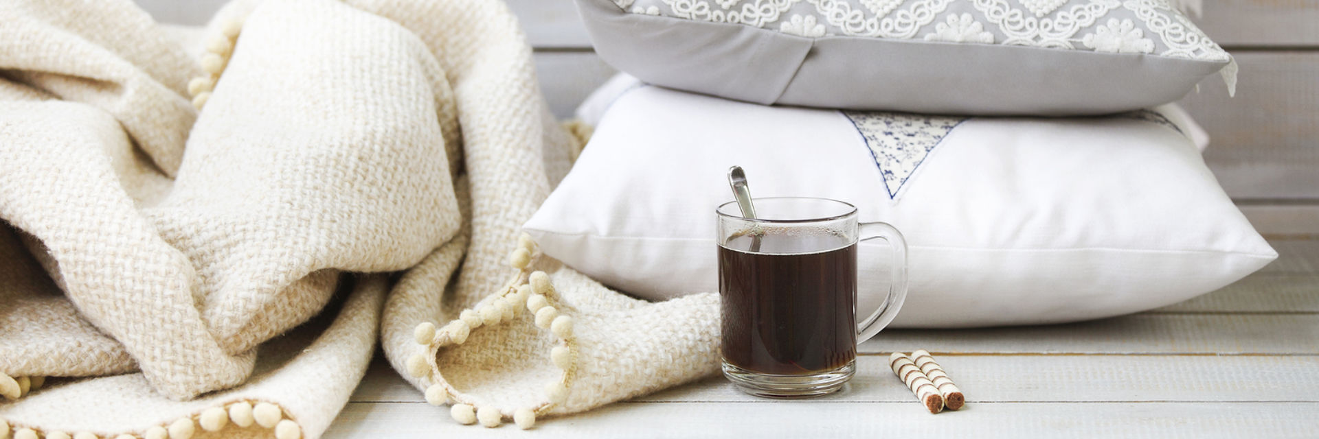 hot drink next to a blanket and two pillows