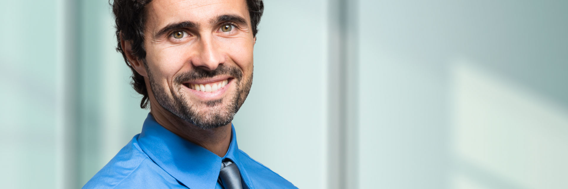 A cheerful middle-aged businessman showing nice white teeth in his smile.