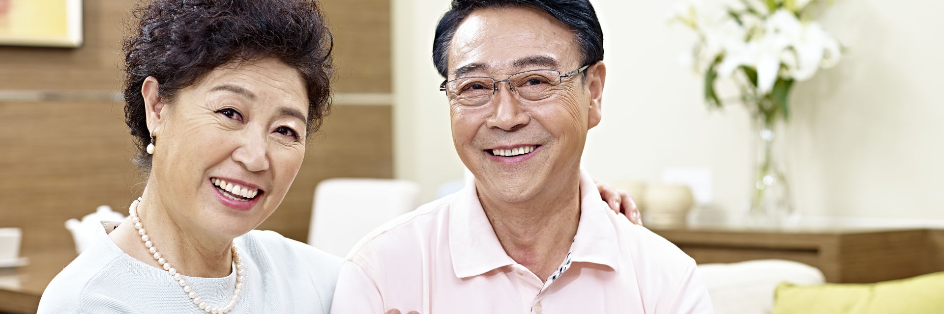 Smiling mature Asian couple with nice teeth after restoration dentistry treatment.