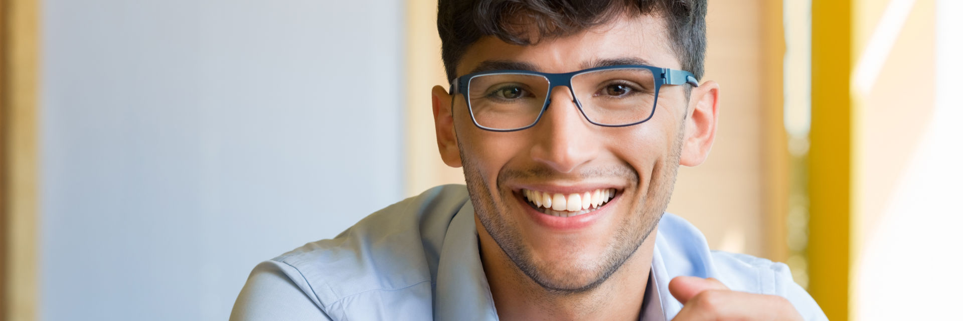 Happy young man wearing glasses showing nice teeth in his smile.