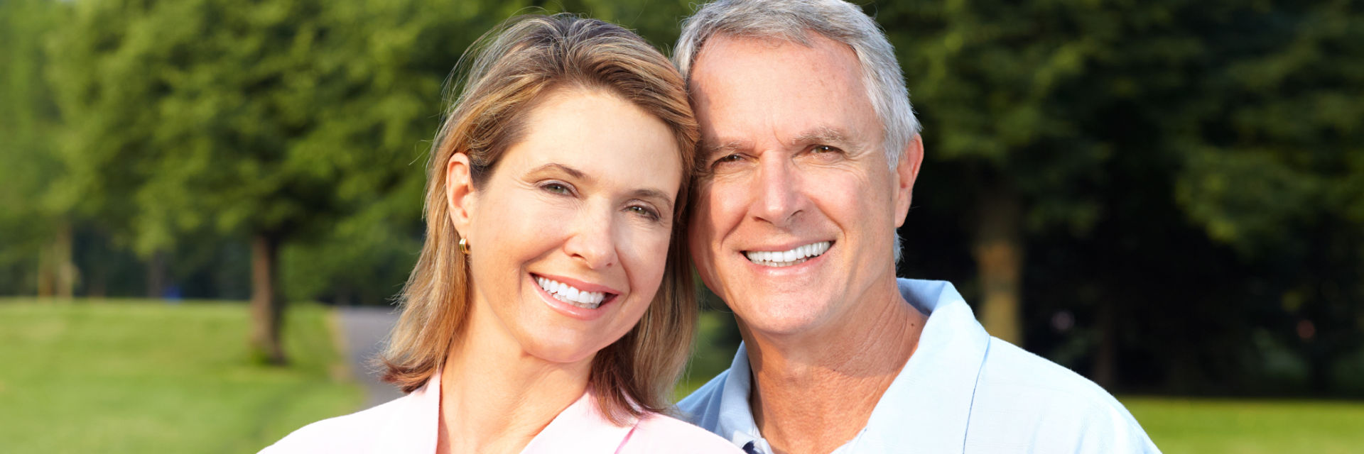 Broadly smiling mature couple showing their perfect teeth after implant restoration.