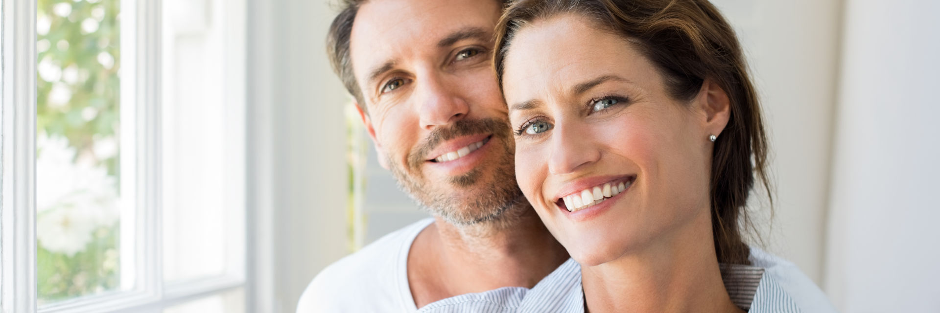 Relaxed middle-aged couple showing nice teeth in their smiles.