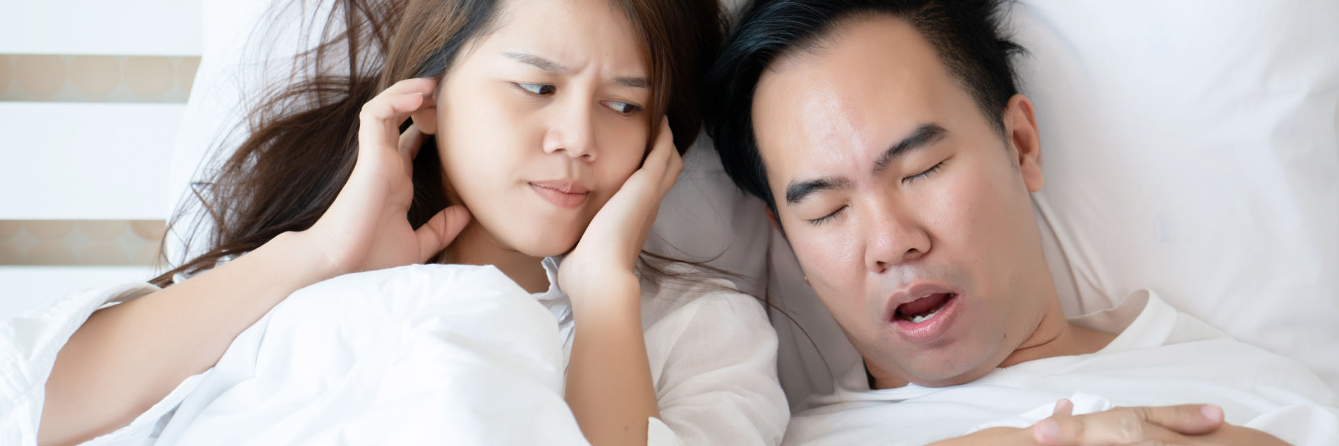 A snoring man sleeping next to an annoyed woman blocking her ears.