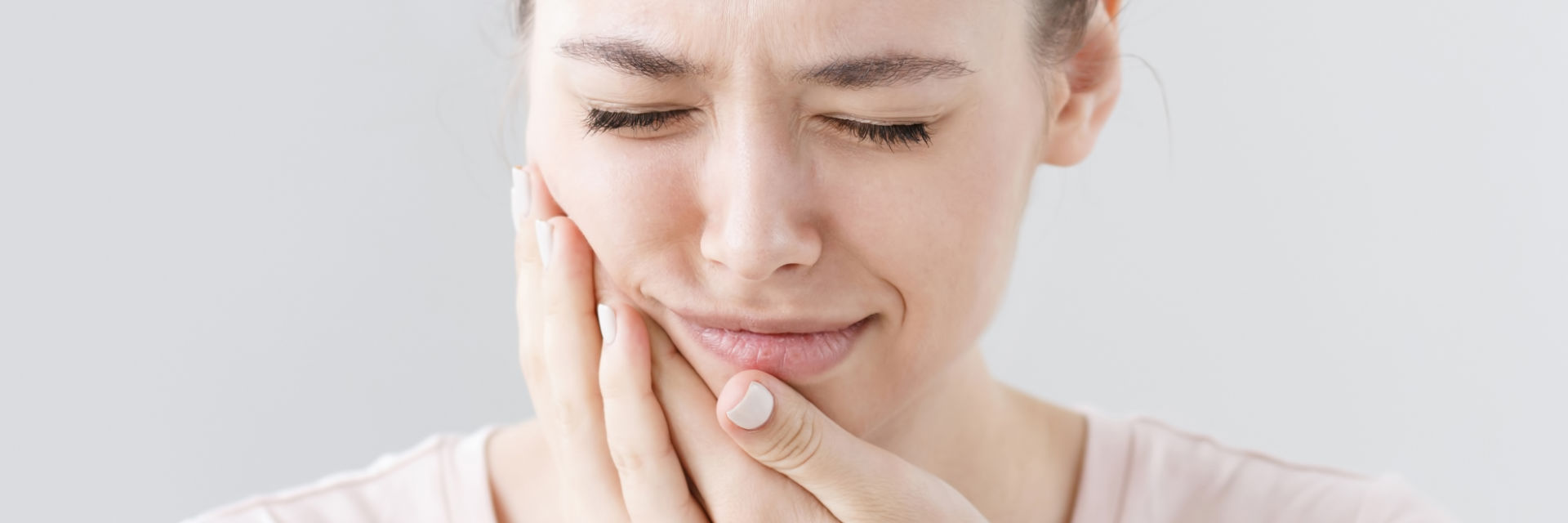 Young woman with severe jaw pain caused by TMJ syndrome.