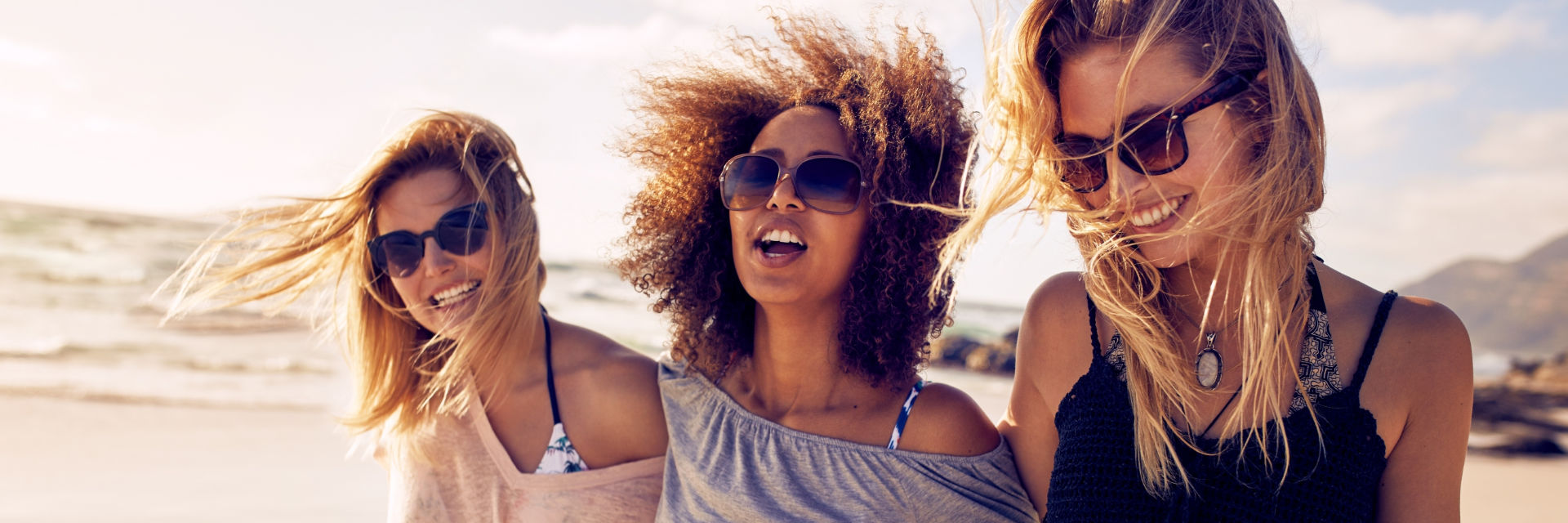 Three young attractive women with perfect smiles spending time on the beach.