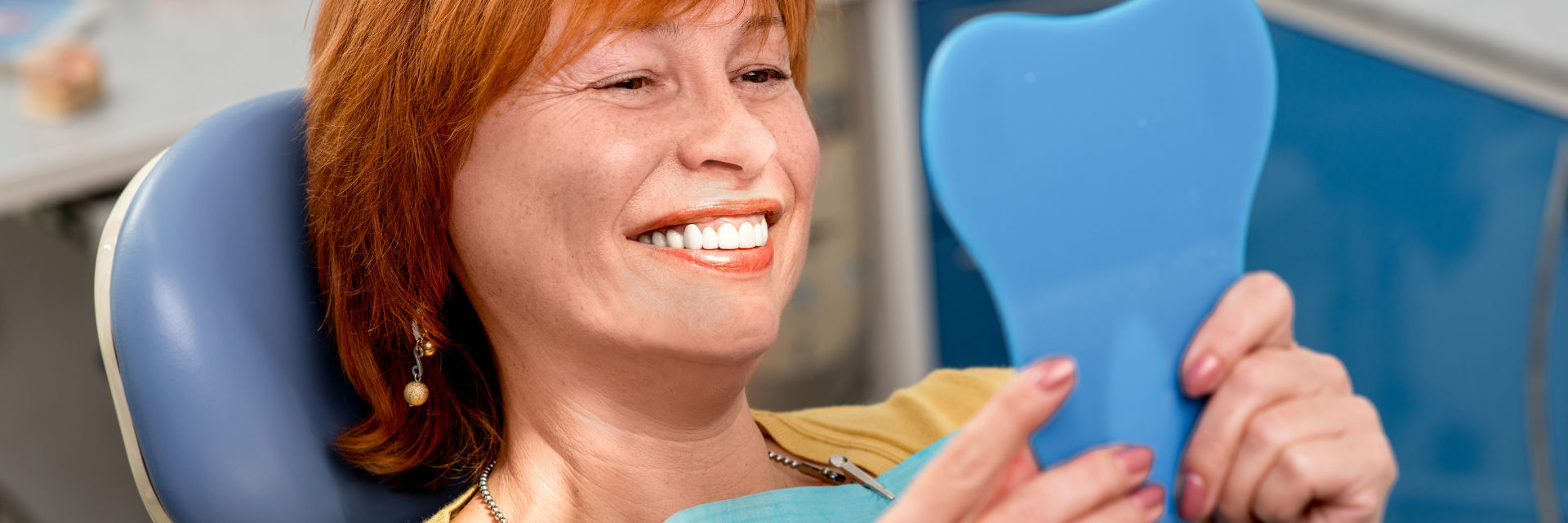 Happy mature woman in a dental chair looking at her beautiful teeth in a mirror.
